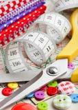 Κουμπιά, ζωηρόχρωμα υφάσματα, ψαλίδι, που μετρούν την ταινία στο ράψιμο του προτύπου Στοκ Εικόνες
