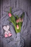Κουνέλι μελοψωμάτων με τις ρόδινες καρδιές και τις ρόδινες τουλίπες σε ένα ξύλινο υπόβαθρο Τοπ άποψη, ελεύθερου χώρου Στοκ Φωτογραφία