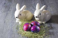 Κουνέλια και αυγά διακοσμήσεων Πάσχας σε ένα γκρίζο υπόβαθρο Στοκ Φωτογραφία