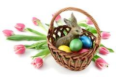 Κουνέλι Πάσχας σε ένα basklet με τα αυγά Πάσχας και τις τουλίπες στο λευκό Στοκ φωτογραφία με δικαίωμα ελεύθερης χρήσης