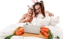 Κουνέλι που βρίσκεται στο κρεβάτι με το lap-top Στοκ φωτογραφία με δικαίωμα ελεύθερης χρήσης