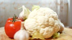 Κουνουπίδι, κολοκύθια, ντομάτα και σκόρδο, που περιστρέφονται σε έναν ξύλινο τέμνοντα πίνακα 4K απόθεμα βίντεο