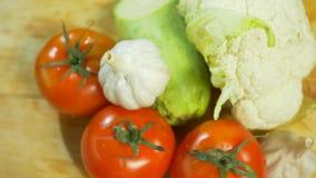 Κουνουπίδι, κολοκύθια, ντομάτα και σκόρδο, που περιστρέφονται σε έναν ξύλινο τέμνοντα πίνακα 4K φιλμ μικρού μήκους