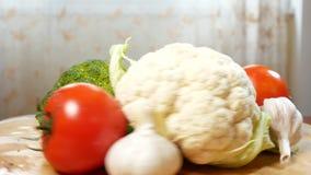 Κουνουπίδι, ντομάτες, μπρόκολο και σκόρδο, που περιστρέφονται σε έναν ξύλινο τέμνοντα πίνακα 4K απόθεμα βίντεο