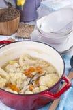 Κουνουπίδι που μαγειρεύεται σε έναν κόκκινο χυτοσίδηρο και μια ανθοδέσμη των τουλιπών Μια μπλε πετσέτα Ελεύθερου χώρου για το κεί στοκ φωτογραφίες με δικαίωμα ελεύθερης χρήσης
