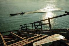 Κουπί χωρικών ένα πέρασμα βαρκών μέσω της σπασμένης γέφυρας Στοκ Φωτογραφίες