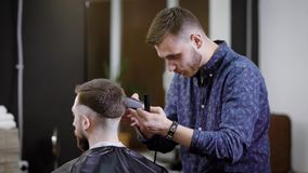 Κουρέας που κάνει το μοντέρνο hairdo στην unrecognizable αρσενική συνεδρίαση πελατών στην καρέκλα στο barbershop απόθεμα βίντεο