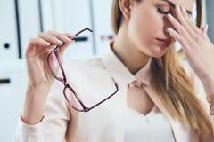 Κουρασμένα καυκάσια eyeglasses εκμετάλλευσης επιχειρηματιών και να τρίψει τη γέφυρα μύτης Κορίτσι που αισθάνεται την ταλαιπωρία α Στοκ εικόνα με δικαίωμα ελεύθερης χρήσης