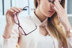 Κουρασμένα καυκάσια eyeglasses εκμετάλλευσης επιχειρηματιών και να τρίψει τη γέφυρα μύτης Κορίτσι που αισθάνεται την ταλαιπωρία α Στοκ εικόνες με δικαίωμα ελεύθερης χρήσης