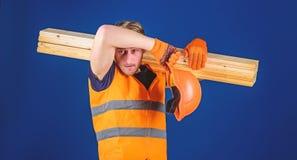Κουρασμένη έννοια εργατών Άτομο στο κράνος και τα προστατευτικά γάντια που σκουπίζουν τον ιδρώτα από το μέτωπο, μπλε υπόβαθρο ξυλ στοκ εικόνες με δικαίωμα ελεύθερης χρήσης