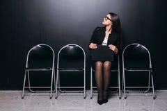 κουρασμένη αναμονή Νέο έγγραφο εκμετάλλευσης επιχειρηματιών και κοίταγμα μακριά καθμένος στην καρέκλα στο μαύρο κλίμα Στοκ Φωτογραφίες