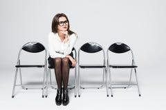 κουρασμένη αναμονή Τρυπημένη νέα επιχειρηματίας που κοιτάζει μακριά καθμένος στην καρέκλα στο γκρίζο κλίμα Στοκ Φωτογραφία
