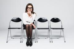κουρασμένη αναμονή Τρυπημένη νέα επιχειρηματίας που κοιτάζει μακριά καθμένος στην καρέκλα στο γκρίζο κλίμα Στοκ Εικόνα