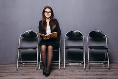 κουρασμένη αναμονή Τρυπημένο νέο έγγραφο εκμετάλλευσης επιχειρηματιών και κοίταγμα μακριά καθμένος στην καρέκλα στο μαύρο κλίμα Στοκ φωτογραφίες με δικαίωμα ελεύθερης χρήσης