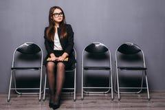 κουρασμένη αναμονή Τρυπημένο νέο έγγραφο εκμετάλλευσης επιχειρηματιών και κοίταγμα μακριά καθμένος στην καρέκλα στο μαύρο κλίμα Στοκ Εικόνες