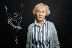 Κουρασμένη ανώτερη γυναίκα που θυμάται τη νεολαία της και που καταπλήσσει τη σταδιοδρομία Στοκ Εικόνα