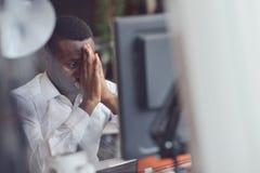 Κουρασμένη αφρικανική συνεδρίαση ατόμων σε ένα γραφείο μετά από μια σκληρή εργάσιμη ημέρα, που λειτουργεί στο lap-top, που προσπα Στοκ φωτογραφίες με δικαίωμα ελεύθερης χρήσης