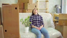 Κουρασμένη γυναίκα με μια συνεδρίαση λουλουδιών στον καναπέ μετά από να κινηθεί απόθεμα βίντεο