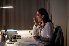 Κουρασμένη γυναίκα με το γραφείο lap-top που χασμουριέται τη νύχτα Στοκ Φωτογραφία