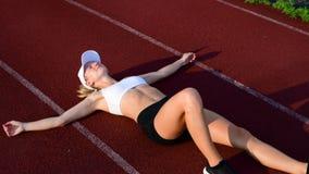 Κουρασμένη γυναίκα που παίρνει ένα υπόλοιπο μετά από το τρέξιμο που βρίσκεται στην τρέχοντας διαδρομή φιλμ μικρού μήκους