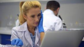 Κουρασμένη γυναίκα που τρίβει τους ναούς ενώ έχοντας τον πονοκέφαλο στο εργαστήριο απόθεμα βίντεο