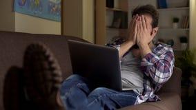 Κουρασμένη ενήλικη συνεδρίαση ατόμων στον καναπέ, κλείνοντας πρόσωπο με τα χέρια, συνεχής αναζήτηση εργασίας στοκ εικόνα με δικαίωμα ελεύθερης χρήσης