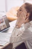 Κουρασμένη επιχειρηματίας με το lap-top και έγγραφα που κάθονται στον πίνακα στην αρχή Στοκ εικόνα με δικαίωμα ελεύθερης χρήσης