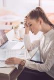 Κουρασμένη επιχειρηματίας με το lap-top και έγγραφα που κάθονται στον πίνακα στην αρχή Στοκ φωτογραφία με δικαίωμα ελεύθερης χρήσης