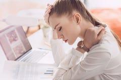 Κουρασμένη επιχειρηματίας με το lap-top και έγγραφα που κάθονται στον πίνακα στην αρχή Στοκ Φωτογραφία