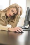 Κουρασμένη επιχειρηματίας που κοιτάζει μακριά καθμένος στο γραφείο υπολογιστών Στοκ εικόνες με δικαίωμα ελεύθερης χρήσης
