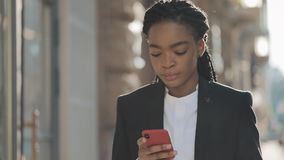 Κουρασμένη επιχειρηματίας που χρησιμοποιεί το smartphone που περπατά στην οδό κοντά στο επιχειρησιακό κέντρο Μαύρος μοντέρνος dre απόθεμα βίντεο
