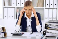 Κουρασμένη επιχειρησιακή γυναίκα ή θηλυκός λογιστής με τους λογαριασμούς και τους φακέλλους εγγράφου στην αρχή Στοκ φωτογραφίες με δικαίωμα ελεύθερης χρήσης