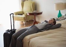 Κουρασμένη επιχειρησιακή γυναίκα που βάζει στο κρεβάτι στο δωμάτιο ξενοδοχείου Στοκ Φωτογραφία