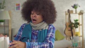 Κουρασμένη η πορτρέτο νέα γυναίκα αφροαμερικάνων με Afro hairstyle με το μαντίλι στο λαιμό είναι άρρωστη sneezes αλλεργία ή κρύα  απόθεμα βίντεο