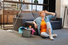 Κουρασμένη και ανήσυχη ελαφρύς-μαλλιαρή γυναίκα στην πορτοκαλιά μπλούζα στοκ φωτογραφία με δικαίωμα ελεύθερης χρήσης