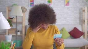 Κουρασμένη και τονισμένη γυναίκα αφροαμερικάνων με ένα afro hairstyle που εξετάζει την τραπεζική κάρτα στα χέρια και να φωνάξει τ απόθεμα βίντεο