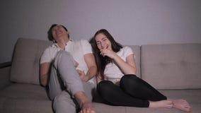 Κουρασμένη και τρυπημένη συνεδρίαση ζευγών lazily σε έναν καναπέ που προσέχει τη νύχτα τη TV φιλμ μικρού μήκους