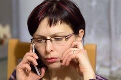 Κουρασμένη κλήση γυναικών τηλεφωνικώς Στοκ φωτογραφία με δικαίωμα ελεύθερης χρήσης