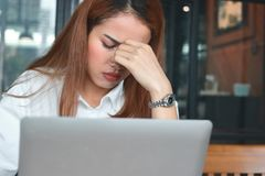 Κουρασμένη νέα ασιατική επιχειρησιακή γυναίκα που πάσχει από αυστηρό από την κατάθλιψη στον εργασιακό χώρο Στοκ Φωτογραφίες