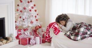 Κουρασμένη νέα γυναίκα κοιμισμένη μπροστά από ένα χριστουγεννιάτικο δέντρο απόθεμα βίντεο