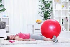 Κουρασμένη νέα γυναίκα που παίρνει το υπόλοιπο μετά από να ασκήσει στοκ εικόνες