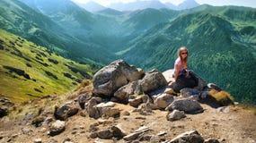 Κουρασμένη ξανθή συνεδρίαση κοριτσιών στα βουνά Στοκ Φωτογραφία