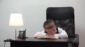 Κουρασμένη συνεδρίαση παιδιών στο γραφείο και ύπνος με το κεφάλι στο βιβλίο, το αστείο πορτρέτο, λίγο μαθητή και μεγάλα eyeglasse απόθεμα βίντεο