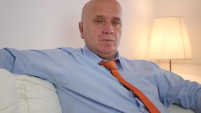 Κουρασμένη τρυπημένη και οκνηρή συνεδρίαση επιχειρηματιών σε έναν καναπέ που χαλαρώνει στο σπίτι απόθεμα βίντεο