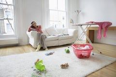 Κουρασμένη χαλάρωση νοικοκυρών στον καναπέ Στοκ Φωτογραφίες