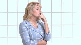 Κουρασμένη ώριμη γυναίκα στο επιχειρησιακό κοστούμι που πάσχει από τον πονοκέφαλο απόθεμα βίντεο