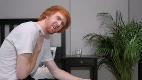 Κουρασμένη Redhead συνεδρίαση ατόμων στην πλευρά του κρεβατιού, πόνος στο λαιμό στοκ εικόνες