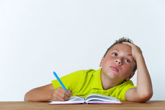 Κουρασμένη tween συνεδρίαση αγοριών με το βιβλίο άσκησης Στοκ Εικόνες