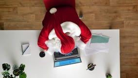 Κουρασμένος Άγιος Βασίλης κοιμισμένος στο γραφείο σε ένα lap-top, εναέρια άποψη, κορυφή κάτω από τον πυροβολισμό, μετακινείται το φιλμ μικρού μήκους