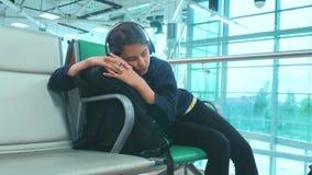 Κουρασμένος έφηβος κοριτσιών στον ταξιδιωτικό ύπνο ακουστικών στον αερολιμένα που περιμένει τον πάγκο πυλών τρόπου ζωής αναχώρηση απόθεμα βίντεο